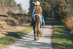 Pretty girl riding her grey horse Royalty Free Stock Images