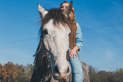 Pretty girl riding her grey horse Stock Photo