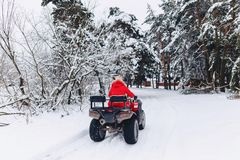 A pretty girl riding a quadrocycle in a picturesque snowy area stock photos