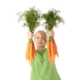 Pretty girl with ripe carrots royalty free stock photography