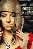 Pretty girl in roman helmet. Pretty sexy girl with ancient roman helmet posing over brick wall Royalty Free Stock Images