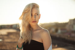 Pretty girl on the roof standing in sunlight at the sunset Stock Photography