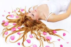 Pretty girl with rose petals in her hair Stock Photos