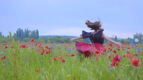 Pretty girl running and dancing in a poppy field smiling happily. Connection with nature. Leisure in nature. Blossoming