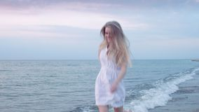 Pretty girl running on the shore and smiling stock video