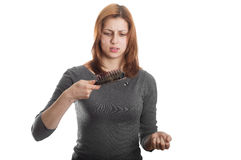 Pretty girl with a sad look on the remaining hair on the comb Stock Photo