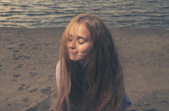Pretty girl on a sandy sea shore, her eyes closed Stock Image