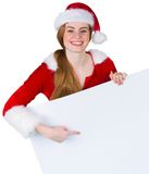Pretty girl in santa costume showing card Royalty Free Stock Image