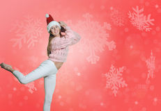 Pretty girl in Santa hat dancing on snowflakes Royalty Free Stock Photo