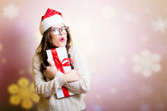 Pretty girl in Santa hat surprised holding giftbox Stock Photography