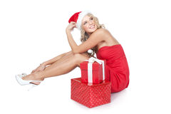 Pretty girl in santa helper hat with red gifts Royalty Free Stock Image