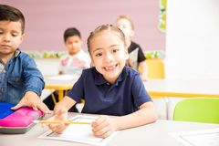 Pretty girl at school with a toothless grin. Portrait of a cute Hispanic little girl attending preschool and smiling with a toothless grin Stock Photos