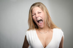 Pretty girl screaming with fingers in ears. Funny portrait of a beautiful young blonde screaming as loud as she can Stock Images