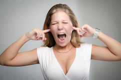 Pretty girl screaming with fingers in ears. Funny portrait of a beautiful young blonde screaming loudly with her fingers in her ears Royalty Free Stock Image