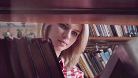Pretty girl searching for a book stock footage