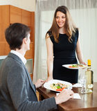Pretty girl serving dinner to  man Stock Photo