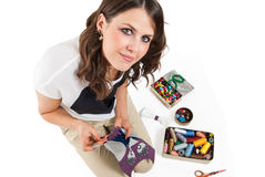 Pretty girl sewing. Fabric on white background Royalty Free Stock Image