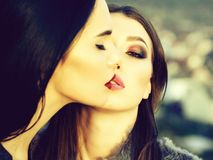 Pretty girl with sexy lips. Two pretty girls young beautiful women models with brunette hair and sexy red lips hold close outdoors stock image