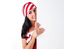 Pretty girl with a sheet of paper. Pretty young brunette woman wearing a Santa's hat hiding behind a blank sheet of paper Royalty Free Stock Photos