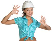 Pretty girl in shirt and white helmet showing ok Stock Photos