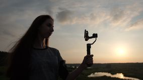 Pretty girl shoots video on the phone with a stabilizer at sunset, slow motion. Pretty girl with long hair shoots video on the phone with a stabilizer. Her stock video footage