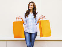 Pretty girl with shopping bags posing against white wall Stock Image