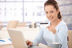 Pretty girl shopping on internet smiling Stock Photography
