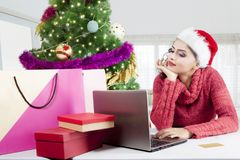 Pretty girl shopping online with a laptop. Picture of an pretty girl shopping online by using a laptop while daydreaming near Christmas tree at home Stock Photos