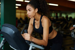 Pretty girl in short sports top kneaded on a stationary bike Stock Image