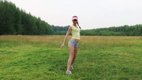 Pretty girl in shorts and cap dances on green meadow. At summer evening stock video footage