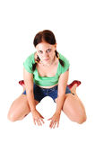 Pretty girl in shorts kneeling on the floor. Stock Photo