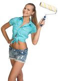Pretty girl in shorts and shirt holding paint. Pretty girl in shorts and shirt standing akimbo, holding paint roller, looking at camera, smiling. Isolated on Stock Photography