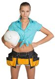 Pretty girl in shorts, shirt and tool belt holding. White helmet in hand. Isolated over white background Royalty Free Stock Image