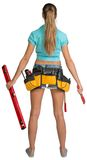 Pretty girl in shorts, shirt and tool belt with. Tools holding red building level and wrench. Full length rear view. Isolated over white background Stock Image