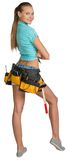 Pretty girl in shorts, shirt and tool belt with Royalty Free Stock Image