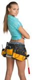 Pretty girl in shorts, shirt and tool belt with. Tools standing with crossed arms. Rear view. Isolated over white background Stock Images