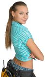 Pretty girl in shorts, shirt and tool belt with. Tools standing with crossed arms. Rear view. Isolated over white background Stock Photos