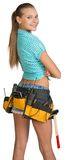 Pretty girl in shorts, shirt and tool belt with. Tools standing with crossed arms. Rear view. Isolated over white background Stock Photo