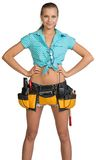 Pretty girl in shorts, shirt and tool belt with. Tools standing with hands on hip. Isolated over white background Royalty Free Stock Photos