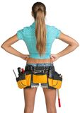 Pretty girl in shorts, shirt and tool belt with. Tools standing with hands on hip. Rear view. Isolated over white background Royalty Free Stock Photography