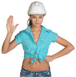 Pretty girl in shorts, shirt and white helmet. Showing stop hand sign. Isolated over white background Stock Photography