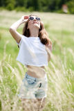 Pretty girl in shorts and a t-shirt in the field among the grass Royalty Free Stock Photography