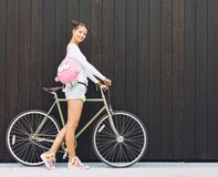 Pretty girl in shorts and t-shirt with a funny pink backpack stands with his bicycle fix gear nex to the wall of wooden planks sun Royalty Free Stock Photos