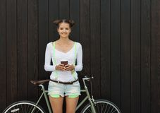 Pretty girl in shorts and t-shirt stands with her bicycle fix gear near the wall of wooden planks bright sunny day Royalty Free Stock Images