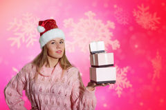 Pretty girl showing gift boxes under snow on Stock Photos