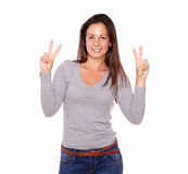 Pretty girl showing victory sign with her fingers Stock Images