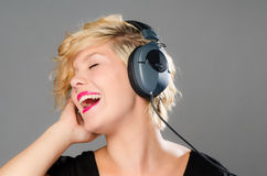 Pretty girl singing along. Beautiful girl listening to music on her headphones, while singing along loudly Stock Image