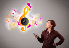 Pretty girl singing and listening to music with musical notes Stock Photos
