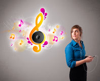 Pretty girl singing and listening to music with musical notes Royalty Free Stock Photo