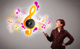 Pretty girl singing and listening to music with musical notes Royalty Free Stock Images
